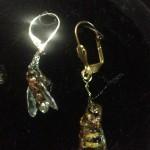 Eine Fliege und eine Biene in Ohrringen verewigt